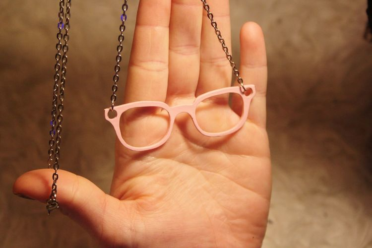 Cropped Hand Holding Chain With Eyeglasses Pendant