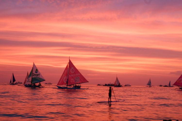 Sailboats sailing in sea against orange sky