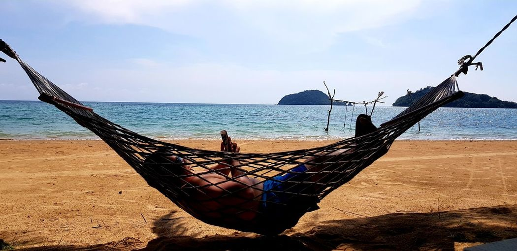 Mature man using mobile phone while relaxing on hammock at beach against sky