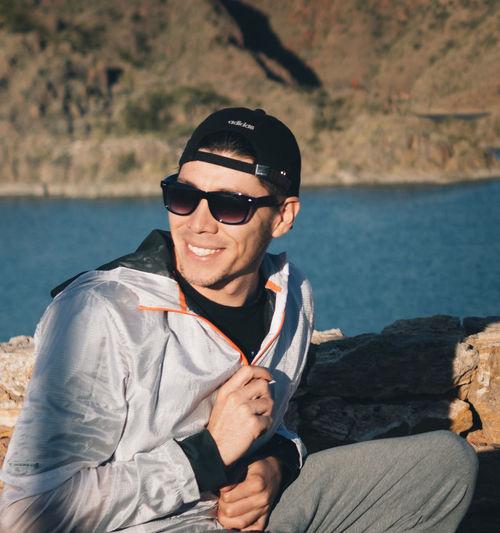 Portrait of smiling man wearing sunglasses at sea shore
