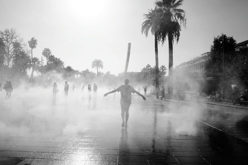 Silhouette of people walking in street fountain