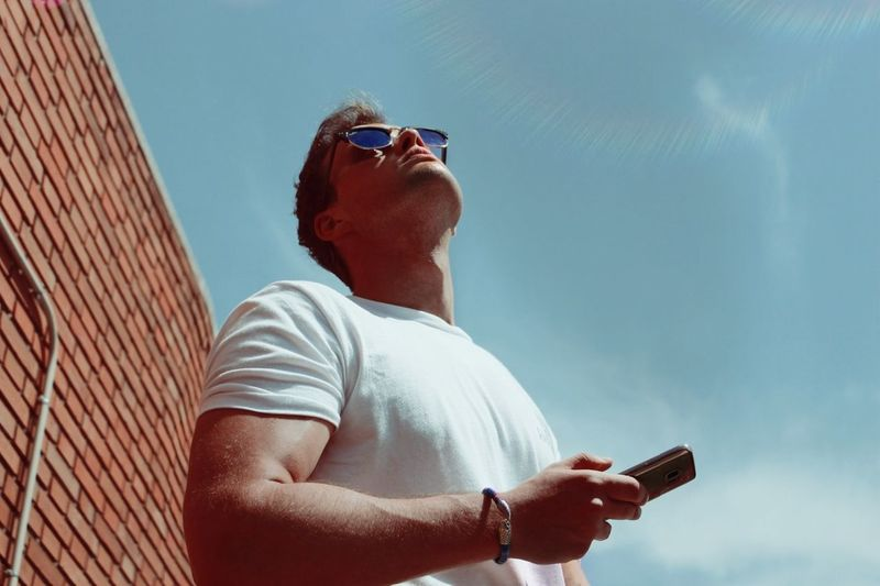 Low angle view of man using mobile phone against sky