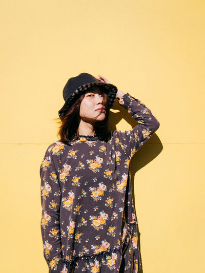 Portrait Of Mid Adult Woman Wearing Hat While Standing Against Yellow Wall