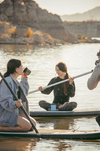 Women sitting on boat in lake