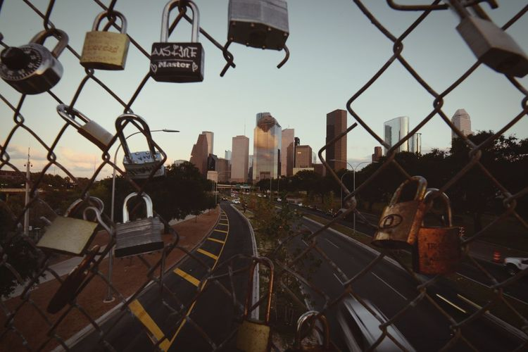Pedestrian bridge locks. Sunset Padlock Locks Houston Fence Architecture Building Exterior Built Structure Chainlink Fence Sky Barrier City No People Cityscape Building Metal Outdoors Transportation Security Day Nature