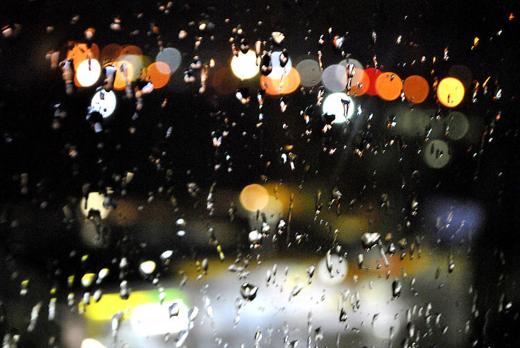 Raindrops on glass window at night