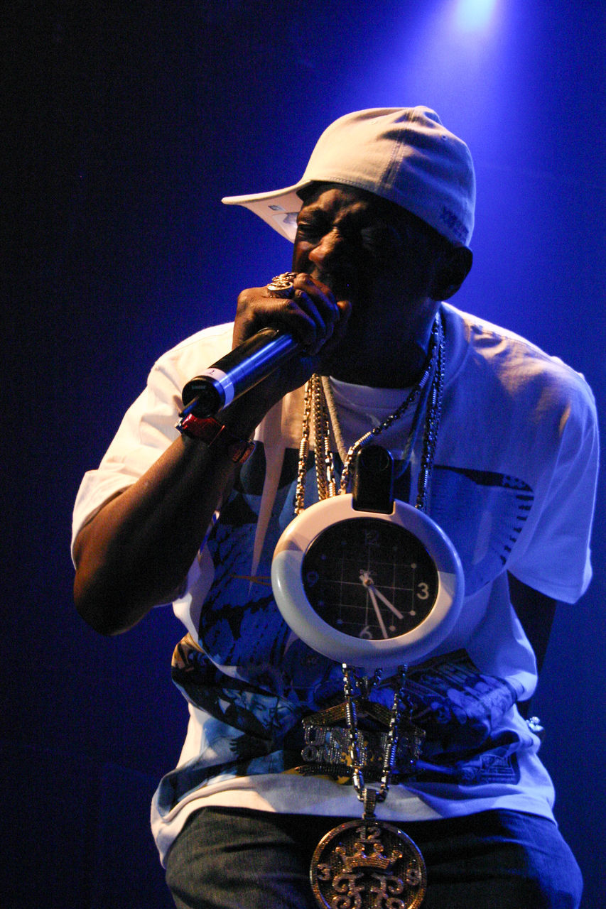 music, musical instrument, musician, arts culture and entertainment, hat, saxophone, performance, jazz music, one person, playing, wind instrument, trumpet, front view, casual clothing, blue, guitar, leisure activity, men, real people, singing, night, outdoors, plucking an instrument, young adult, adult, people
