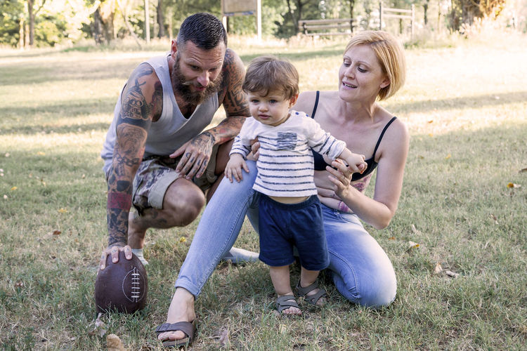 Smiling father and mother with son holding rugby ball at park