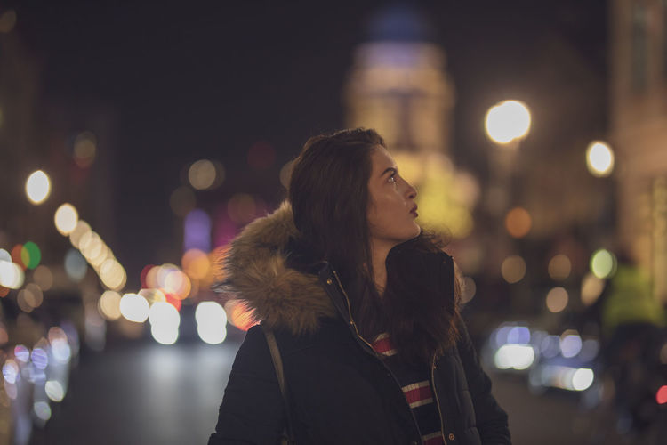 Thoughtful young woman standing on street in illuminated city at night