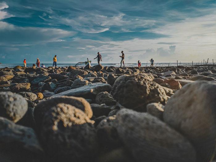 People on rocks at beach against sky