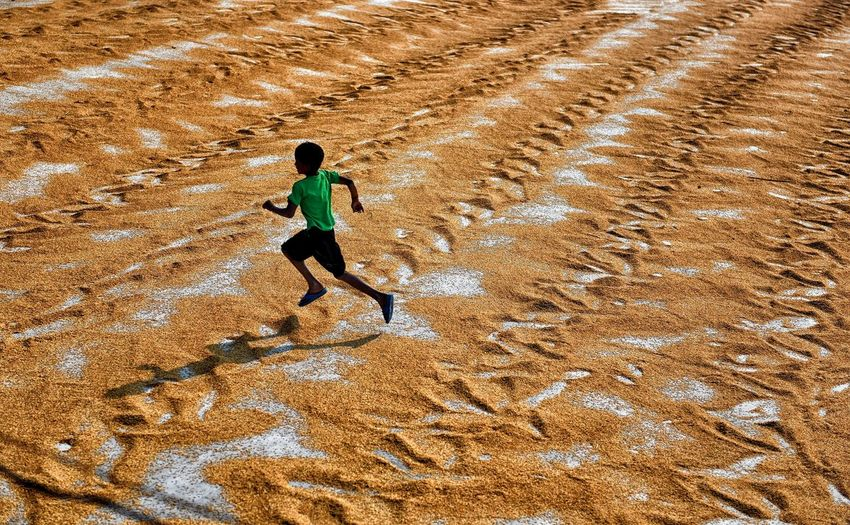 High angle view of boy running on sand