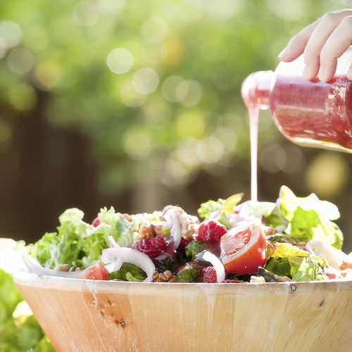 Cropped hand pouring dressing in bowl of salad