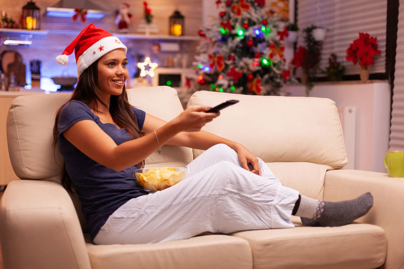 Young woman using phone while sitting on sofa