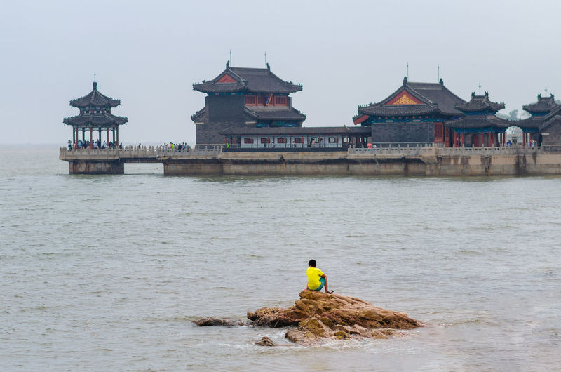 Rear view of man working in sea against building