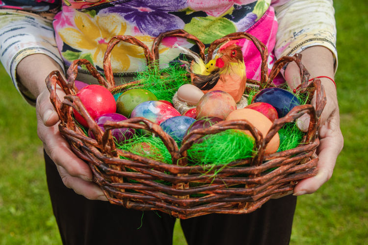 Midsection of woman holding colorful basket