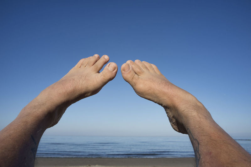 Low angle view of hands on sea against clear blue sky