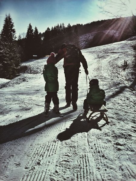 Father Dad And Kids Wintersports Toboggan In Winter Ski Skiing Daughter Son Learning Family Together Sunbeams Long Shadows Winter