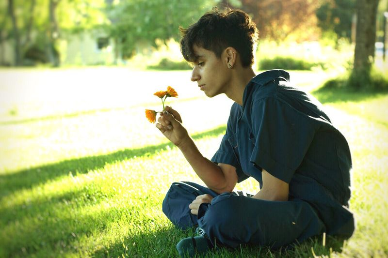 Side View Of Teenage Boy Holding Flowers While Sitting On Grassy Field In Park