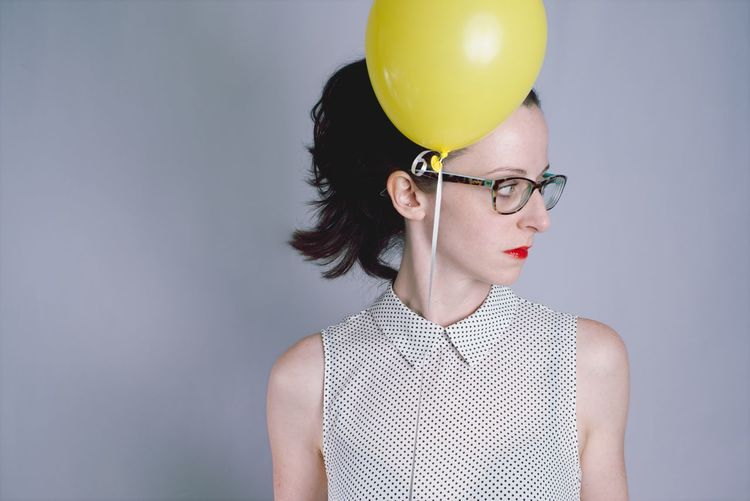 Close-Up Of Young Woman With Balloon Against Gray Background