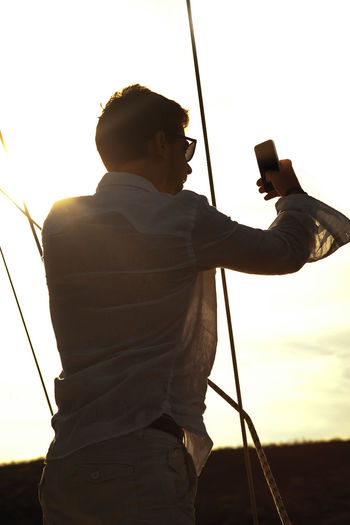 Man taking selfie while standing against sky