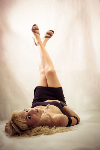 Portrait Of Sensual Woman Lying With Feet Up Against White Background