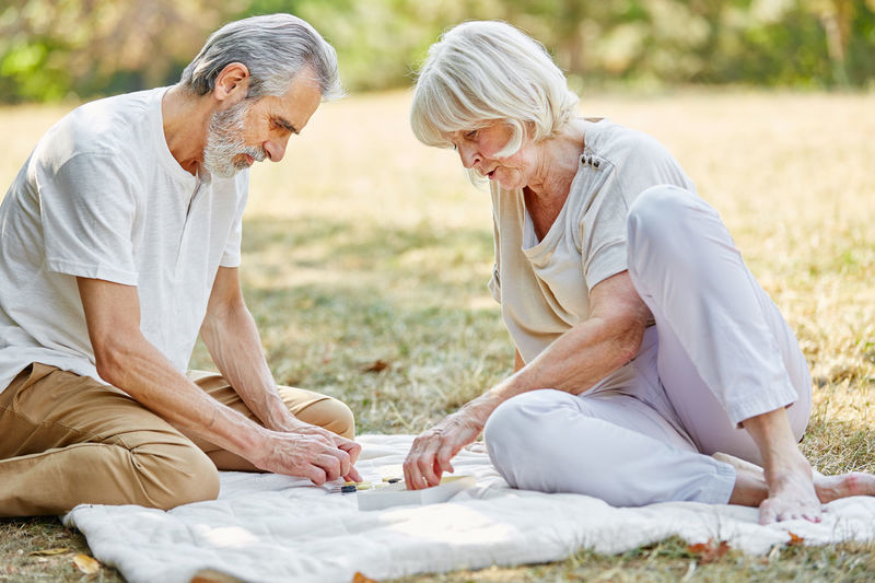 Senior couple adjusting objects on field at park