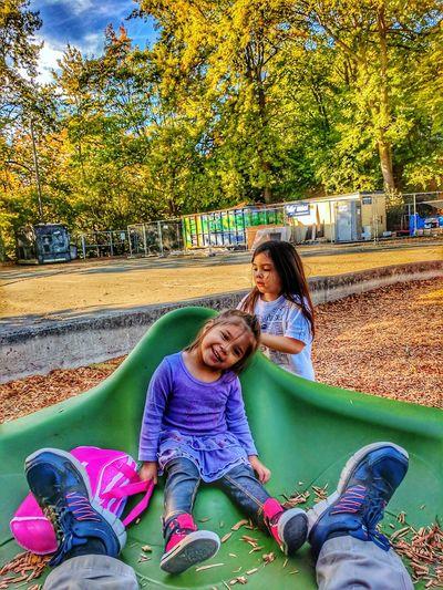 Full length of happy friends sitting on slide at park
