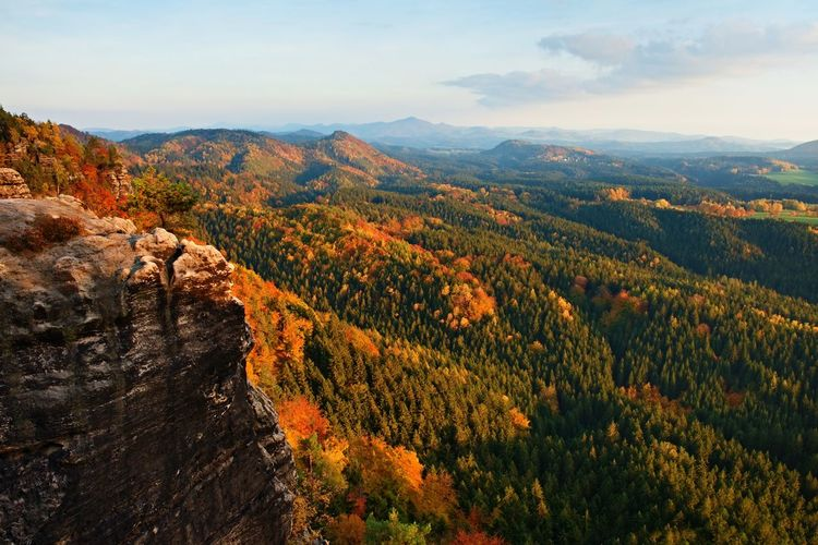 Autumn sunset view over colorful rocks to fall valley of bohemian switzerland.