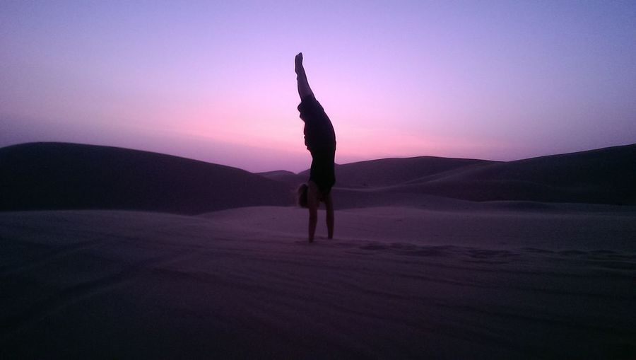 Silhouette man handstand on sand against sky during sunset