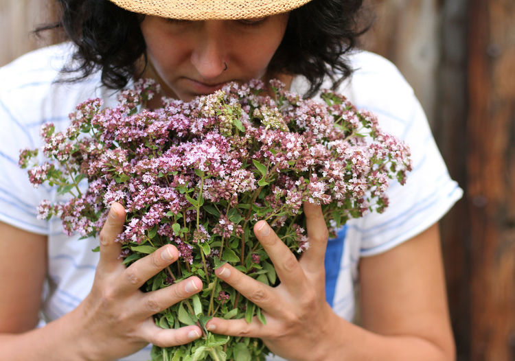 Midsection of woman holding purple flowering plant