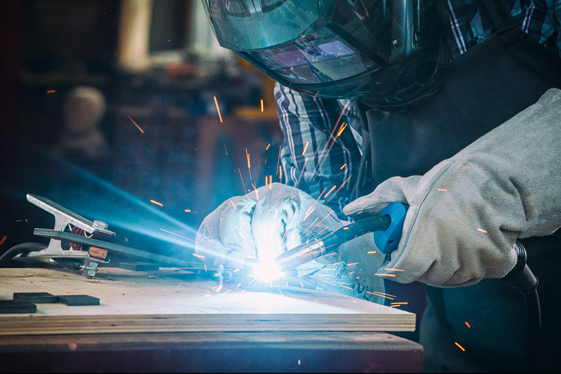 Strong man welder in work clothes hard working and welds with a welding machine metal