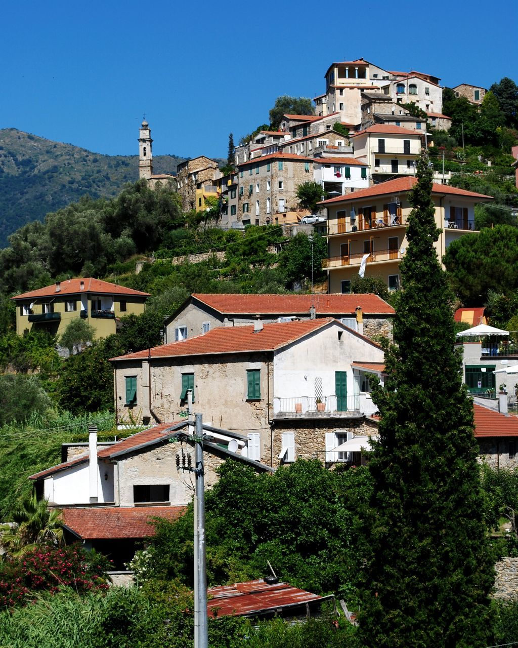 Low Angle View Of Houses And Trees On Hills Against Clear Blue Sky At Dolcedo