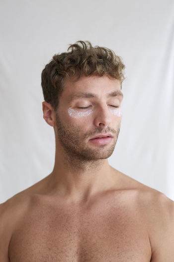 Close-up portrait of shirtless man against white background
