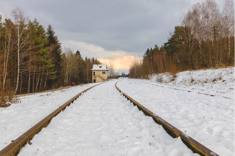 Snow covered railroad tracks by trees against sky