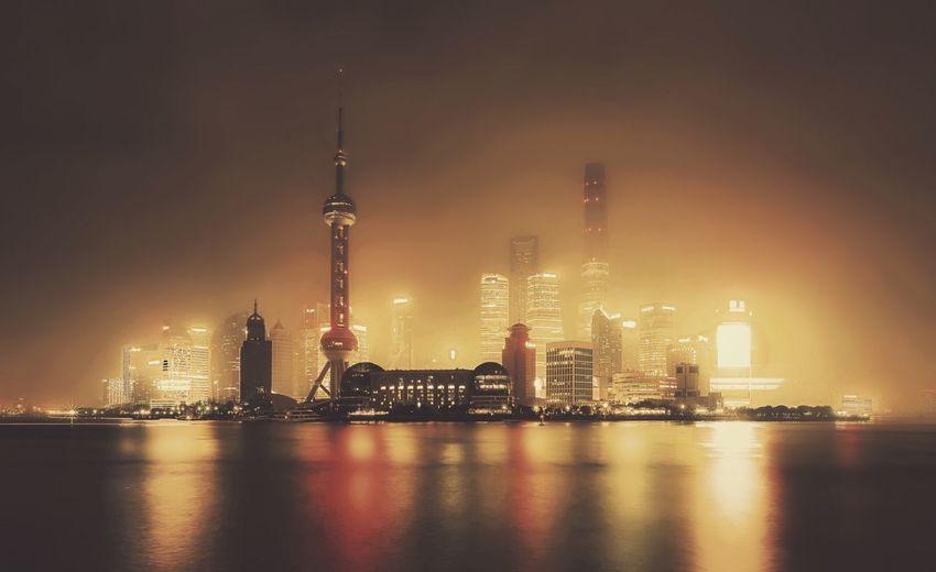 Illuminated City By River At Night