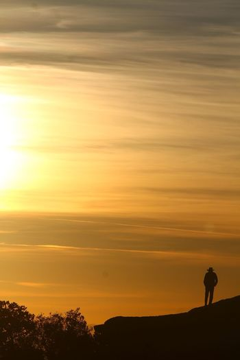 Silhouette of man standing on mountain at sunset