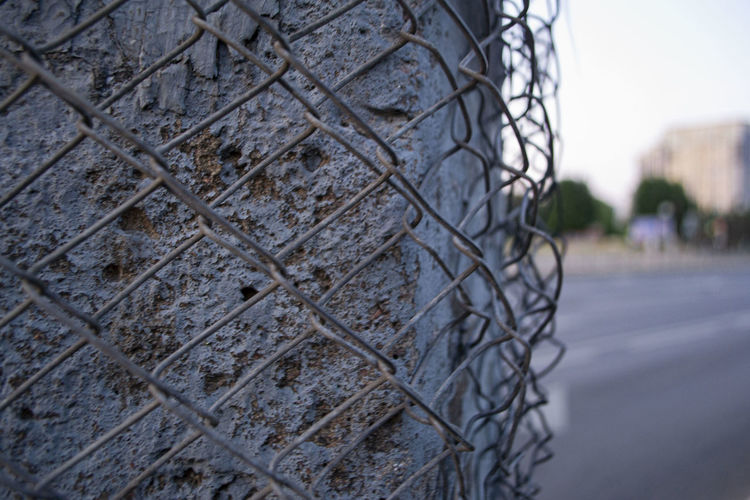 Close-up of metal fence against wall