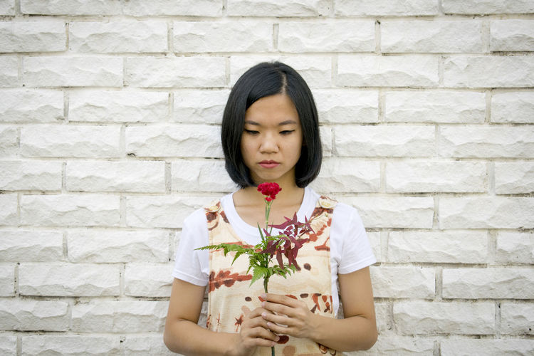 Portrait of young woman holding rose against wall
