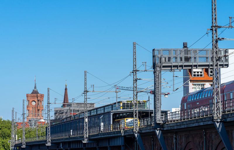 Low angle view of cranes and buildings against clear blue sky