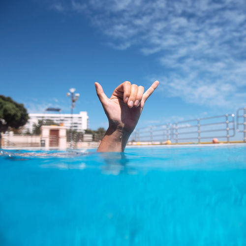 Cropped Hand Gesturing Horn Sign In Swimming Pool Against Sky