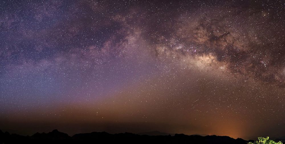 Silhouette landscape against star field at night