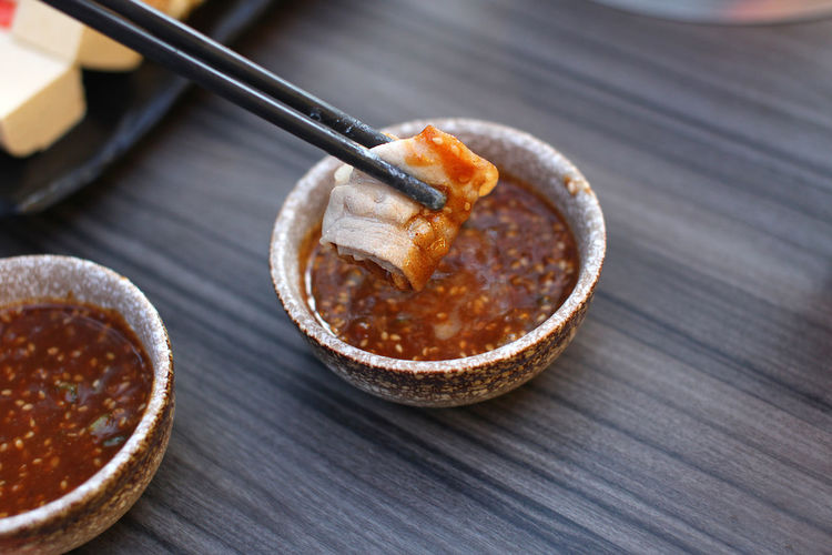 High angle view of food in chopsticks over bowl on table