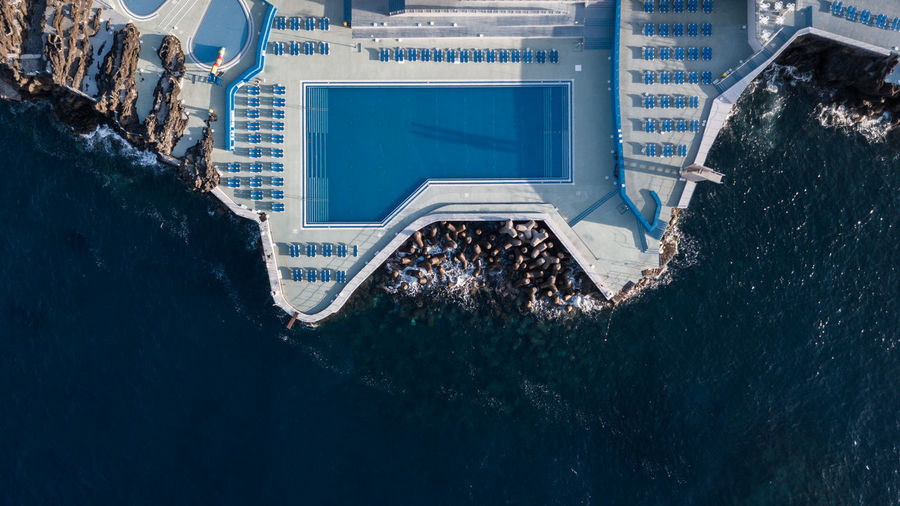 Aerial view of swimming pool on building by sea