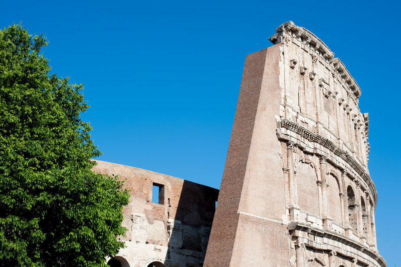 Low angle view of colosseum  against clear blue sky