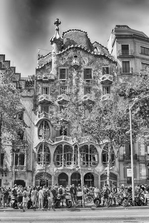 BARCELONA - AUGUST 9: Facade of the modernist masterpiece Casa Batllo, renowned building designed by Antoni Gaudi and iconic landmark in Barcelona, Catalonia, Spain, on August 9, 2017 Architecture Building Exterior Built Structure Group Of People Building Crowd City Sky Large Group Of People Tree Day Nature Real People Plant Travel Destinations Incidental People History The Past Men Outdoors