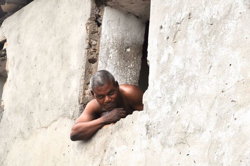 Portrait of shirtless man against wall