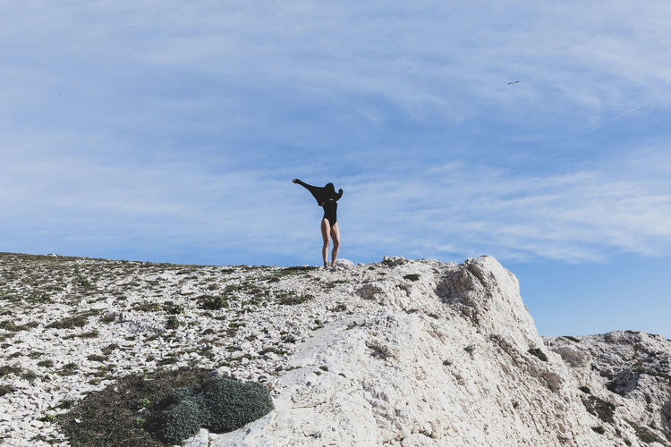Full length of woman standing on cliff