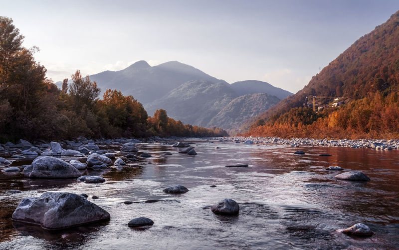 Scenic river and mountainous landscape panorama in Italy Water Mountain Beauty In Nature Scenics - Nature River vanishing point Landscape Nature Sky Tranquil Scene No People Pebble Flowing Water Flowing Mountain Range Outdoors Autumn colors Forest Italy