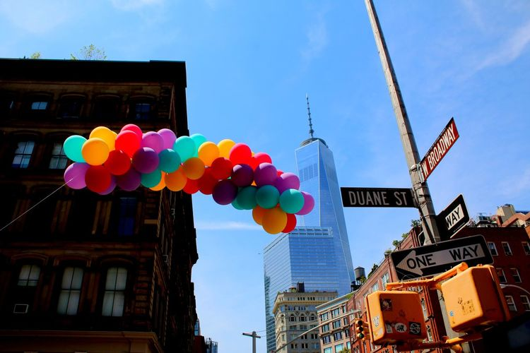 Low Angle View Of Balloons And Road Sign Against One World Trade Center