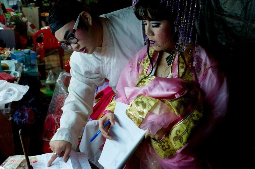 Backstage | Singapore - performers check the sequence of events for tonight's performance.